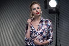 Beautiful slender blonde big breast girl without a bra wearing u. Nbuttoned checkered shirt and jeans on a striped gray background near the studio lamp. Copy Stock Photography