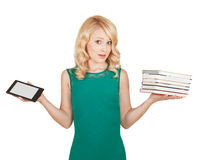 The beautiful, slender blonde compares a tablet and books Stock Images