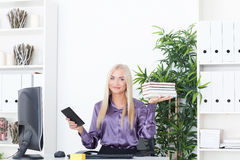 Beautiful, slender blonde compares a tablet and books at office Royalty Free Stock Image