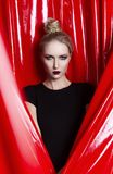 Beautiful slender blonde girl dressed in a black fitting dress on a background of red latex fabric. Fashionable, conceptual,. Commercial and advertising design royalty free stock photography