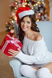 Beautiful slender brunette girl in a Santa hat sits in a cozy ar. Mchair, smiling and holding a gift in the background of New Year`s lights. Christmas Stock Images