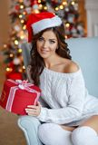 Beautiful slender brunette girl in a Santa hat sits in a cozy ar. Mchair, smiling and holding a gift in the background of New Year`s lights. Christmas Royalty Free Stock Photo