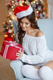 Beautiful slender brunette girl in santa hat sits in a cozy armc. Hair, smiling and looking at a gift on the background of New Year`s lights. Christmas Stock Photography