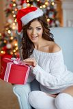 A beautiful slender brunette girl in a Santa hat sits in a cozy. Armchair, smiling and opens a gift against the backdrop of New Year`s lights. Christmas Royalty Free Stock Photography