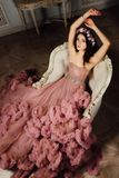 A beautiful slender brunette woman in a pink dress with flounces is sitting on a blue velvet armchair. Luxurious sexy girl in an evening cloudy dress sitting on Royalty Free Stock Images