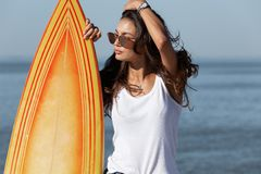 Beautiful slender dark-haired girl in sunglasses standing near by a yellow surfboard on the sandy beach near the sea. royalty free stock photography