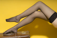 Beautiful slender female legs and suitcase. Beautiful slender female legs in black stockings on old brown suitcase on yellow studio background, horizontal Royalty Free Stock Photo