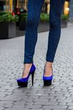 Beautiful slender female legs in tight jeans and blue shoes on a Royalty Free Stock Image