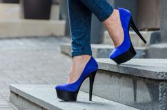 Beautiful slender female legs in tight jeans and blue velvet high-heeled shoes royalty free stock photography