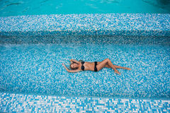 Beautiful slender girl with blond hair in a swimsuit lying in the pool, top view Stock Photography