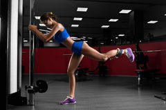 Beautiful slender girl doing exercises in the gym. Beautiful slender brunette girl in blue sportswear doing exercises in the gym. Concept of sport and a healthy stock photo