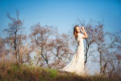 Beautiful slender girl with light brown hair in a long light dress on a background of nature, dry trees, green grass, blue sky in. Summer, in the spring royalty free stock images