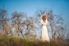 Beautiful slender girl with light brown hair in a long light dress on a background of nature, dry trees, green grass, blue sky in. Summer, in the spring stock photo