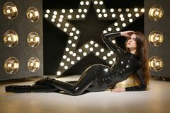 Hot fashionable photomodel posing in latex stylish catsuit and high heels boots stock photo