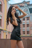 Beautiful and slender girl talking on a cell phone on a city str Royalty Free Stock Photography