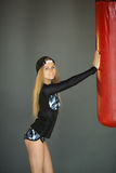 Beautiful slender girl. Beautiful slender young girl near the punching bag in the gym Stock Photography