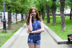 Beautiful and slender teen girl is in the park. And talking on the phone. Young happy woman. Overall plan Stock Photography