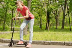 Beautiful slender teenage girl riding a scooter Royalty Free Stock Image