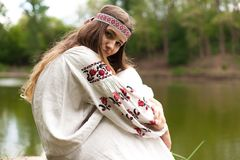 Steep slender Ukrainian woman resting sitting on a stump on the. Beautiful slender Ukrainian in embroidery on the shore of the pond enjoys the nature of a summer Stock Image