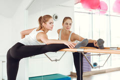 Beautiful slender woman in sportswear stretching near the ballet barre. royalty free stock image