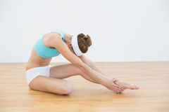 Beautiful slender woman wearing sportswear stretching her leg. Sitting on the floor stock photo