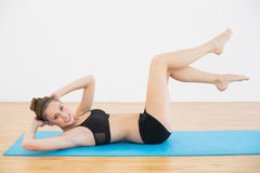Beautiful slender woman wearing sportswear training lying on the floor Royalty Free Stock Images