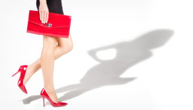 Beautiful slender womanish feet are in red shoes. Shade from a model in complete growth Royalty Free Stock Image