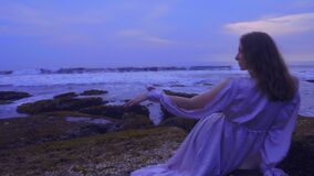 Beautiful young female in a long sexy dress is sitting on the rocks on the ocean beach on Bali on the sunset with wonderful view. Beautiful slender young female stock footage