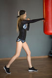 Beautiful slender young girl. Beats a boxing pear in the gym Stock Images
