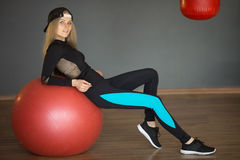 Beautiful slender young girl. Beautiful slender girl in a sport suit in a graceful pose having a rest after training on a sport ball Stock Photo