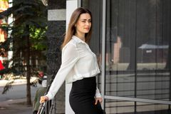 Beautiful slender young lady in a white shirt and black skirt stock image