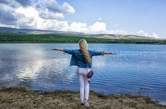 A beautiful slender young woman stands with her back on the shore near the water and admires the beautiful landscape royalty free stock image