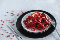 Beautiful slices of juicy red pomegranate on a gray table with Cutlery stock image