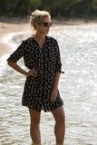 Blonde woman stand in water at the beach in short dress, and sunglasses. Backlight. stock image