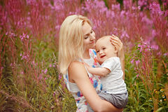 Beautiful slim blonde mom hugs adorable smiling baby boy on the stock image