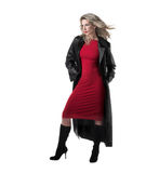 Beautiful,slim blonde woman, red dress, black coat. A beautiful, blonde, slim woman in vivid colours Royalty Free Stock Images