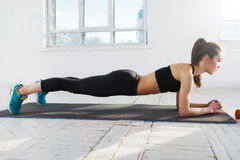 Beautiful slim brunette doing some push ups a the gym. Beautiful young slim woman doing push ups at the gym royalty free stock image