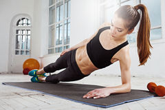 Beautiful slim brunette  doing some push ups a the gym. Beautiful young slim woman  doing push ups at the gym with orange dumbbells Stock Image