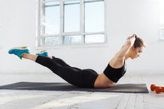 Beautiful slim brunette  doing some stretching exercises in a gym Stock Image