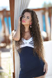 Beautiful slim brunette girl model with makeup and long wavy hair, near beach bed at the beach on vacation. royalty free stock image