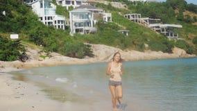 Beautiful slim brunette girl runs on tropical beach in slow motion. 1920x1080. Beautiful slim brunette girl runs on the beach in slow motion. 1920x1080, hd stock video