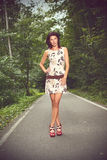 Beautiful slim brunette in a nature. Beautiful slim brunette in a dress posing on a road, in a forest, fashion photography Royalty Free Stock Image