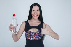 Beautiful slim brunette young girl sports clothes on gray background.Sporty healthy model holding a bottle of water and show royalty free stock photo