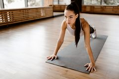 Beautiful slim dark-haired girl dressed white sports clothes is doing is doing plank in the gym stock photography