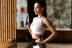 Beautiful slim dark-haired girl dressed in white sports top holds the bottle of water in the gym stock image
