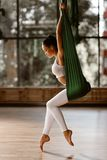 Beautiful slim dark-haired girl dressed in white sports top and tights is doing stretching exercise on green hammock royalty free stock image