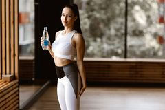 Beautiful slim dark-haired girl dressed in white sports top  and tights holds the bottle of water in the gym royalty free stock photo