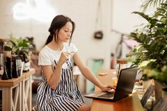 A beautiful slim dark-haired girl with glasses,wearing casual style, types something on her laptop in a cozy coffee shop royalty free stock image