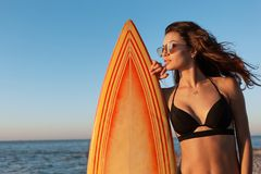 Beautiful slim dark-haired girl in a swimsuit and sunglasses stands near yellow surfboard on a sunny day royalty free stock photos