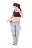 Beautiful slim excited woman in big jeans with isolated on white Royalty Free Stock Photos